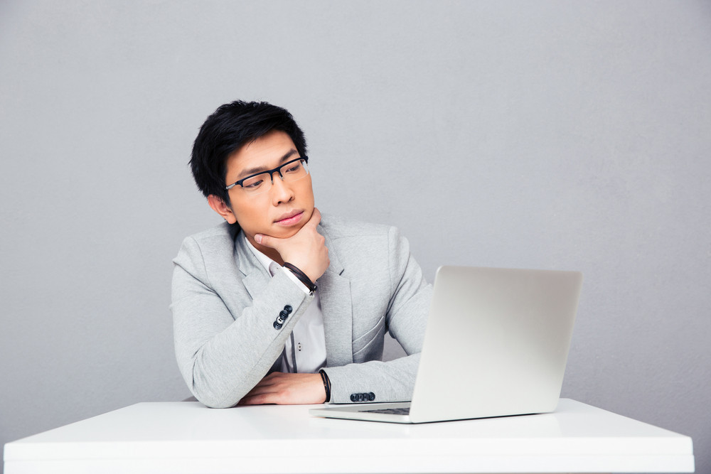 Thoughtful businessman sitting at the table with laptop