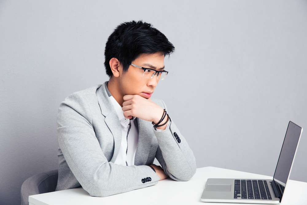 Pensive businessman sitting at the table with laptop