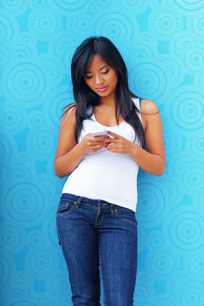 Young happy asian woman with smartphone standing against blue background