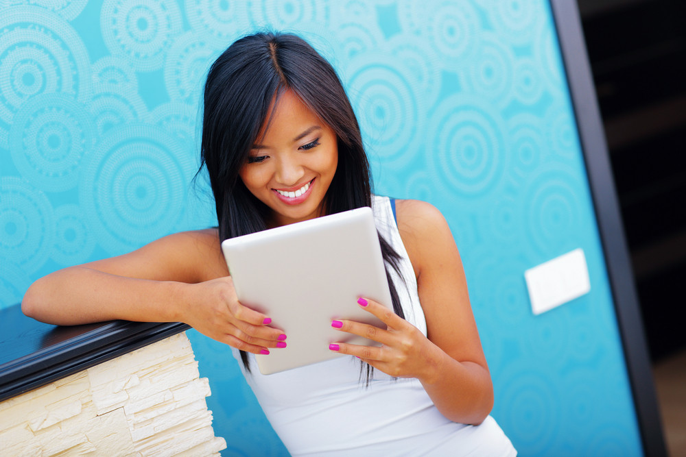 Young happy asian woman using tablet at home