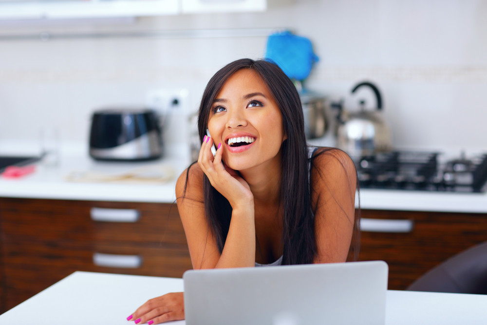 Laughing young asian woman talking on phone at home