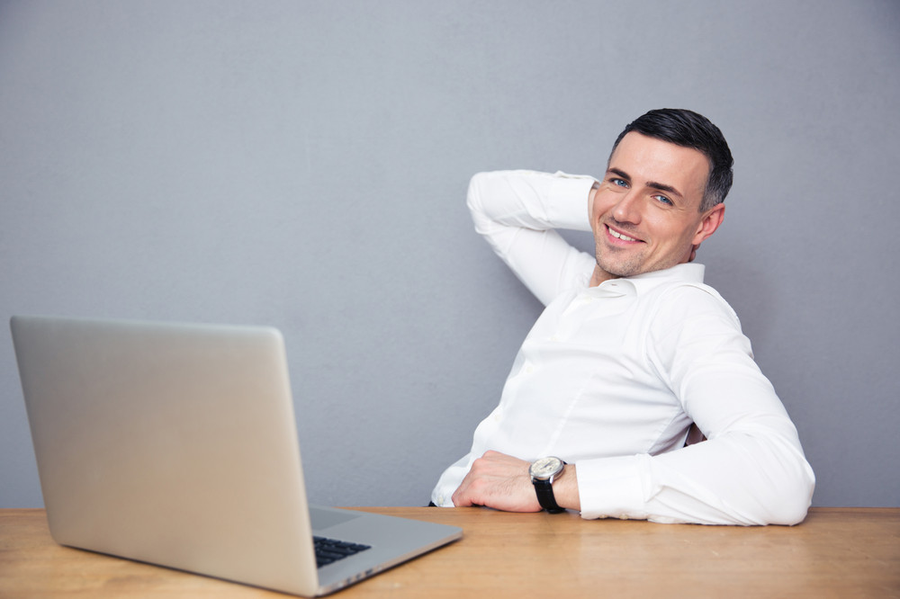 Businessman sitting at the table with laptop