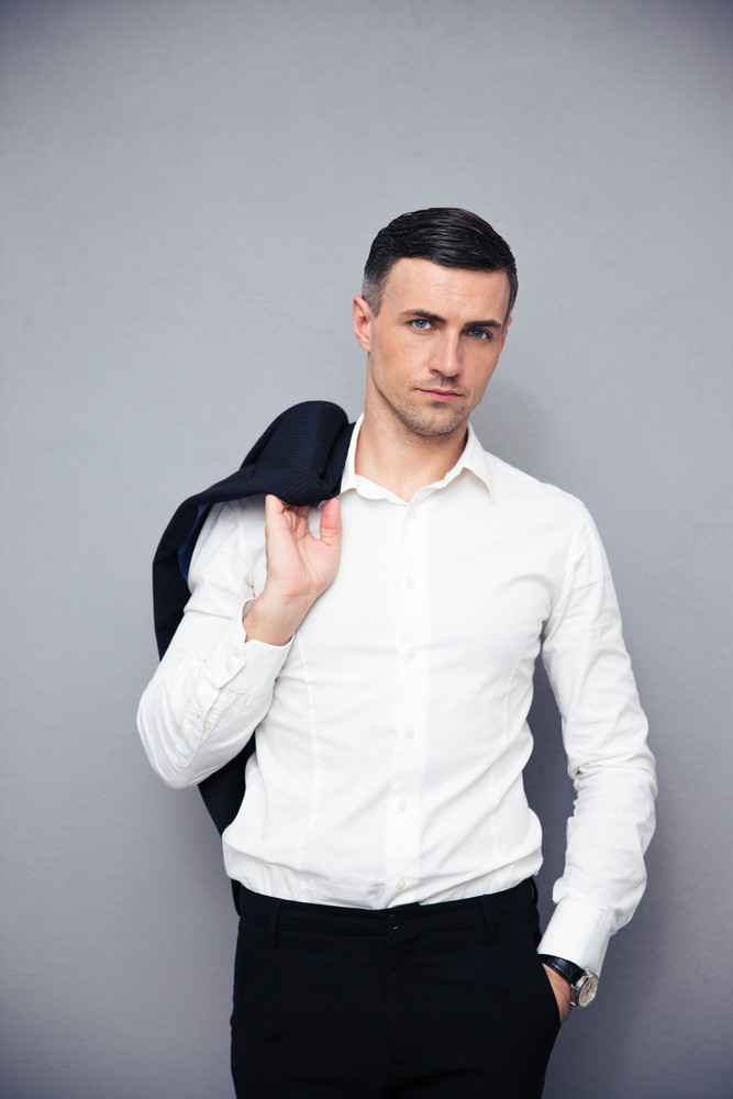 Pensive businessman holding jacket on shoulder