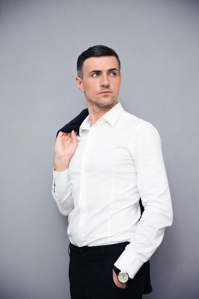 Pensive businessman holding jacket on shoulder