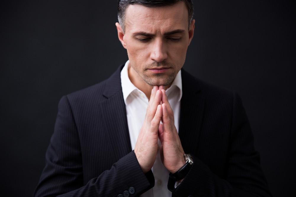 Portrait of a businessman praying