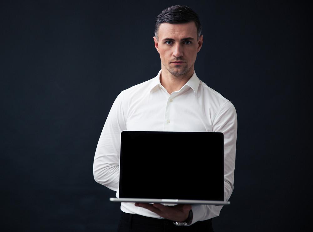 Businessman showing blank laptop screen
