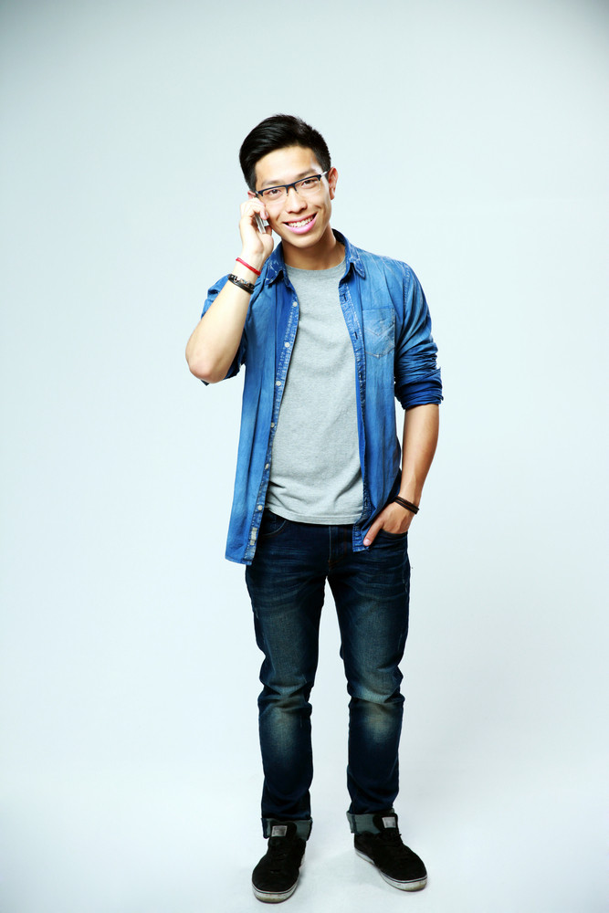 Full length portrait of a young asian man talking on the phone