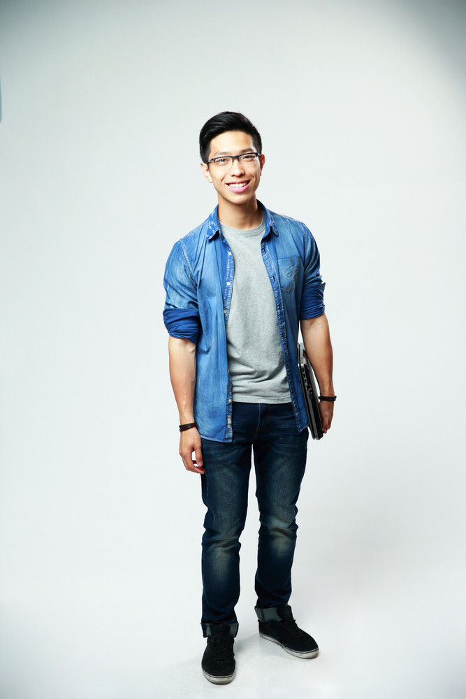 Full length portrait of a happy asian man standing with laptop on gray background