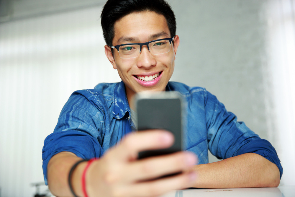 Portrait of a happy asian man sitting at the table with smartphone