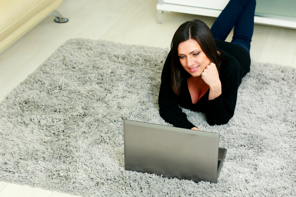 Young happy woman sitting on the floor with laptop at home