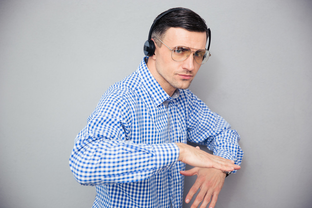 Portrait of a stylish man in glasses and headphones