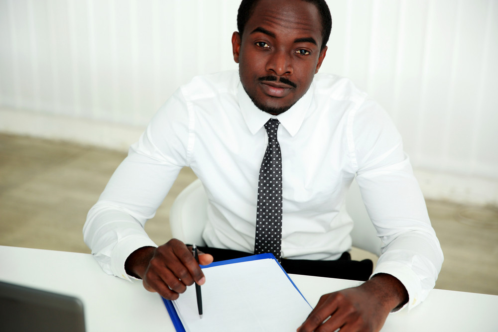 Pensive african man sitting at the table and signing document in office