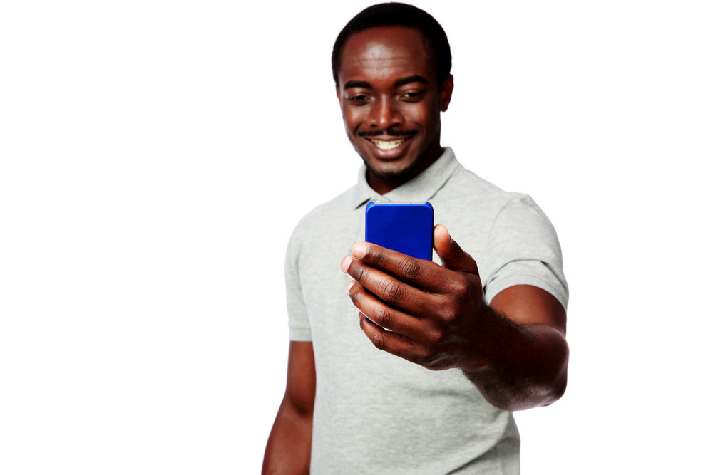 Portrait of a smiling african man using smartphone over white background