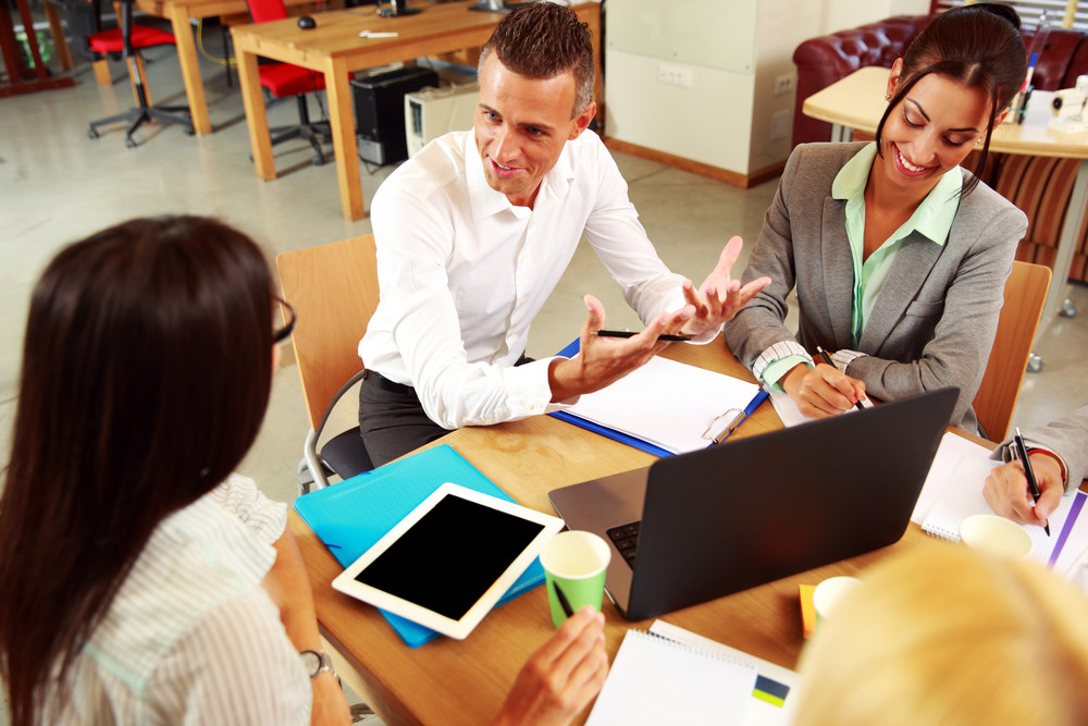 Happy business people having meeting around table in office