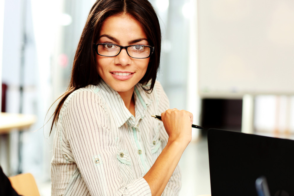 Portrait of a young happy businesswoman sitting at the table in office