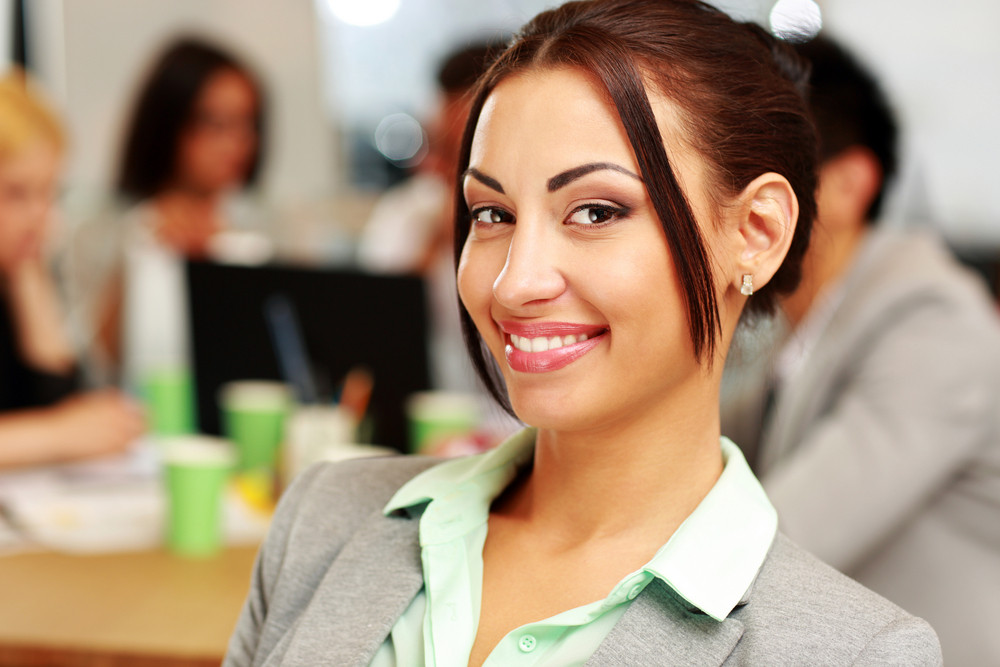 Portrait of a smiling businesswoman in front of colleagues