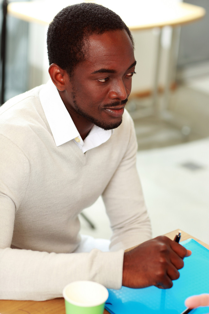 Portrait of african man sitting at the table in office