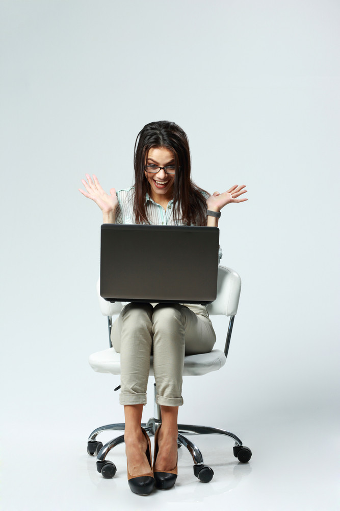 Young happy surprised businesswoman with laptop sitting on chair on gray background