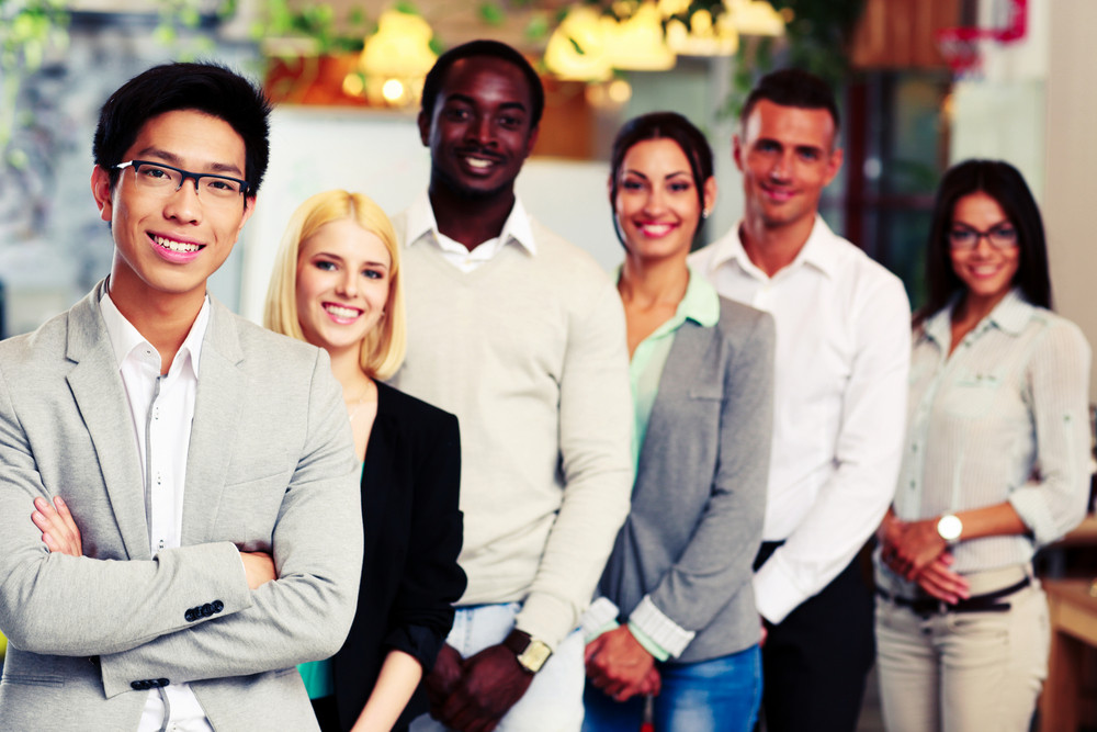 Portrait of a smiling asian businessman standing in front of colleagues