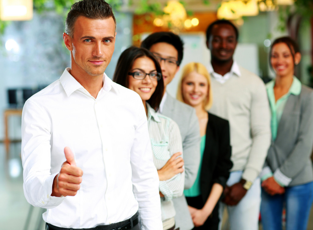 Businessman giving thumb up to camera in front of colleagues