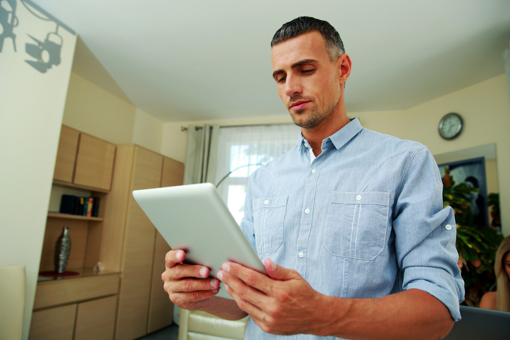 Handsome man standing and using tablet computer at home