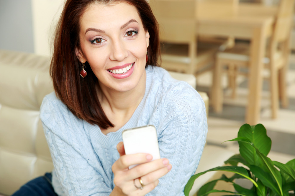 Happy woman holding smartphone at home