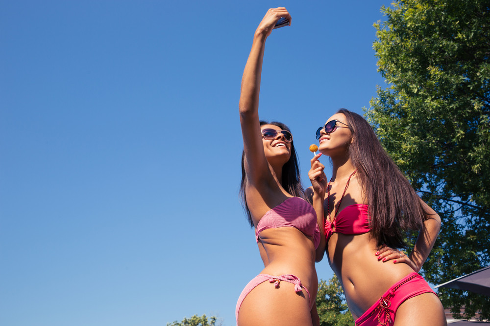 Two woman in swimsuit making selfie photo