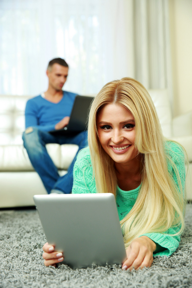 Young couple relaxing at home with electronic equipment