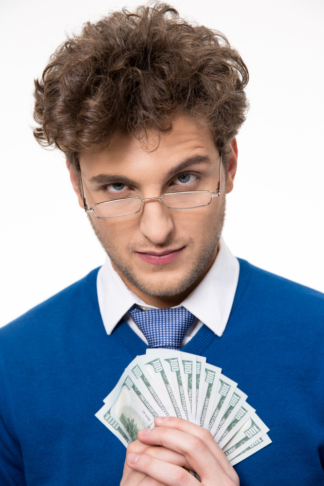 Happy businessman in glasses holding money over gray background
