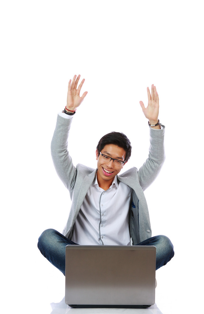 Excited Asian man using laptop on the floor over white background