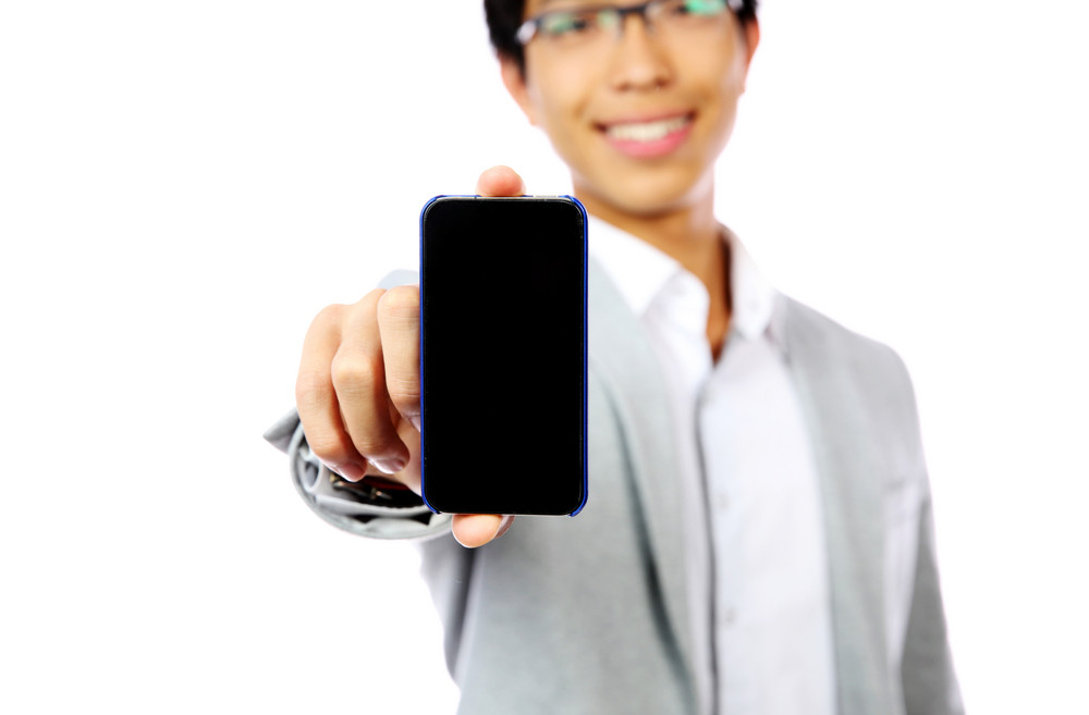 Smiling asian man holding smartphone over white background. Focus on smartphone