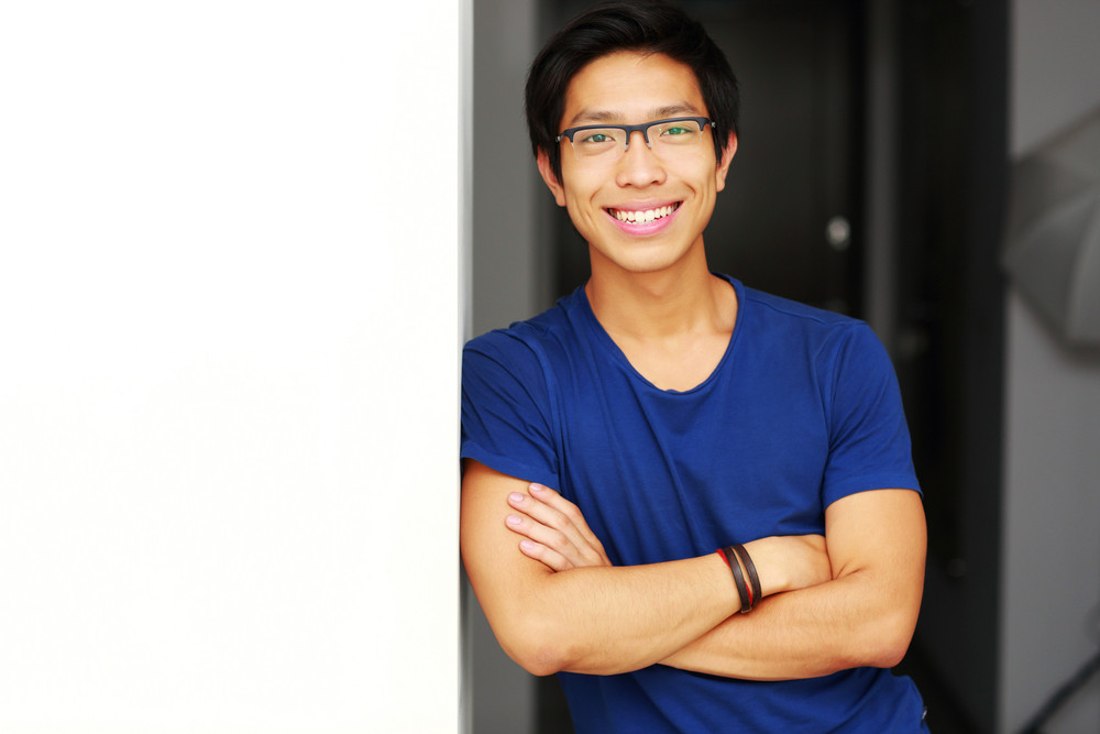 Smiling asian man standing with arms folded at home
