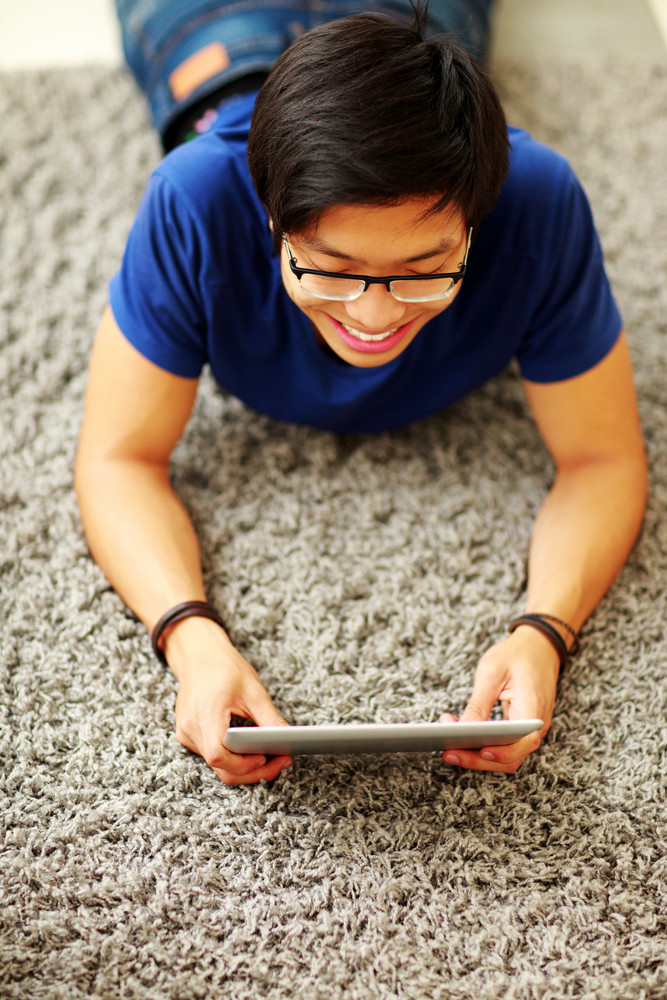 Smiling asian man lying on the floor with tablet computer