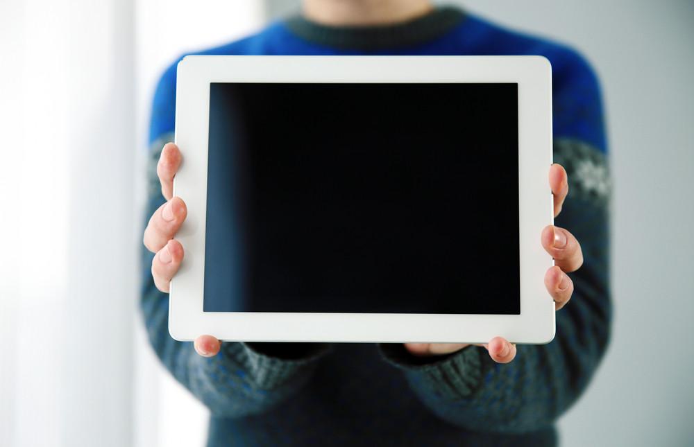 タブレットコンピュータの画面を示す男性の手のクローズアップの肖像画