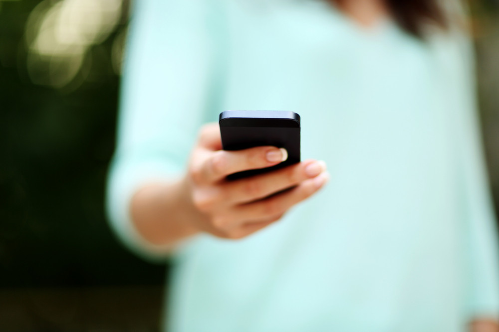 Closeup portrait of a woman using smartphone
