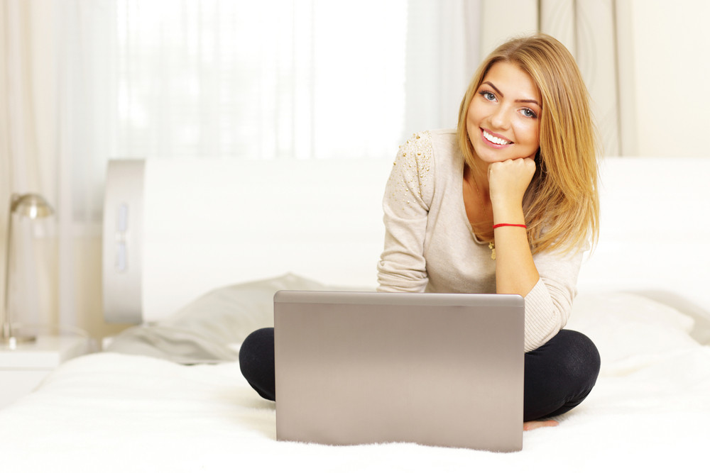Young beautiful woman sitting on the bed with laptop at home
