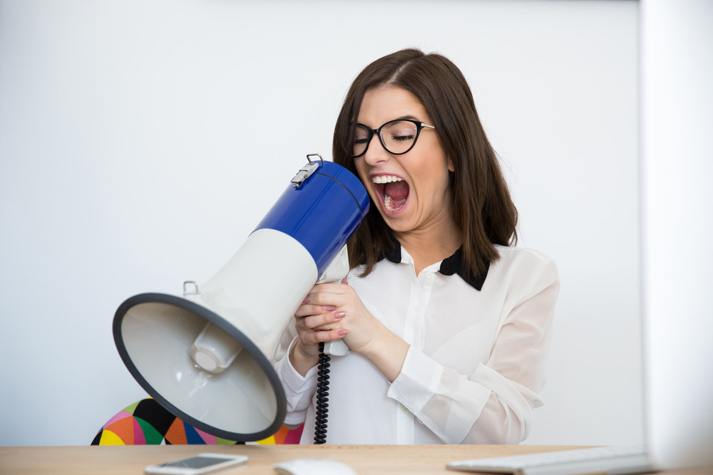 Businesswoman sitting at the table and speaking through megaphone