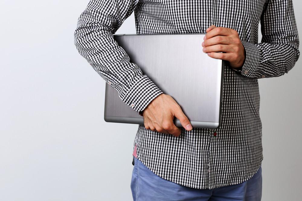 Closeup image of a man holding laptop