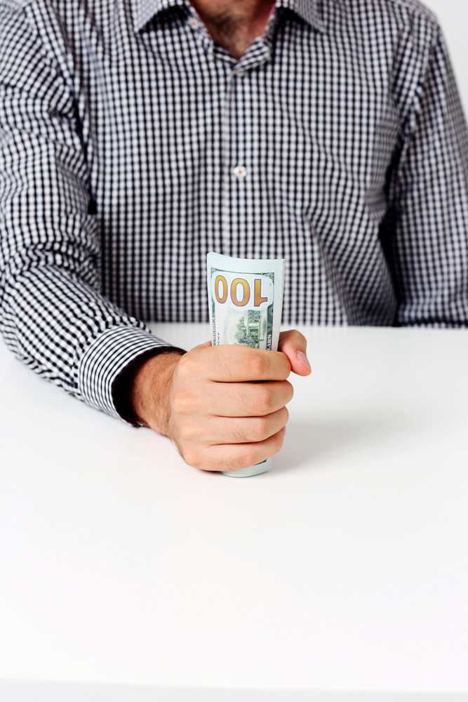 Image of businessman holding banknotes at desk