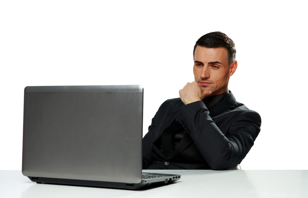 Confident businessman working on laptop isolated on a white background