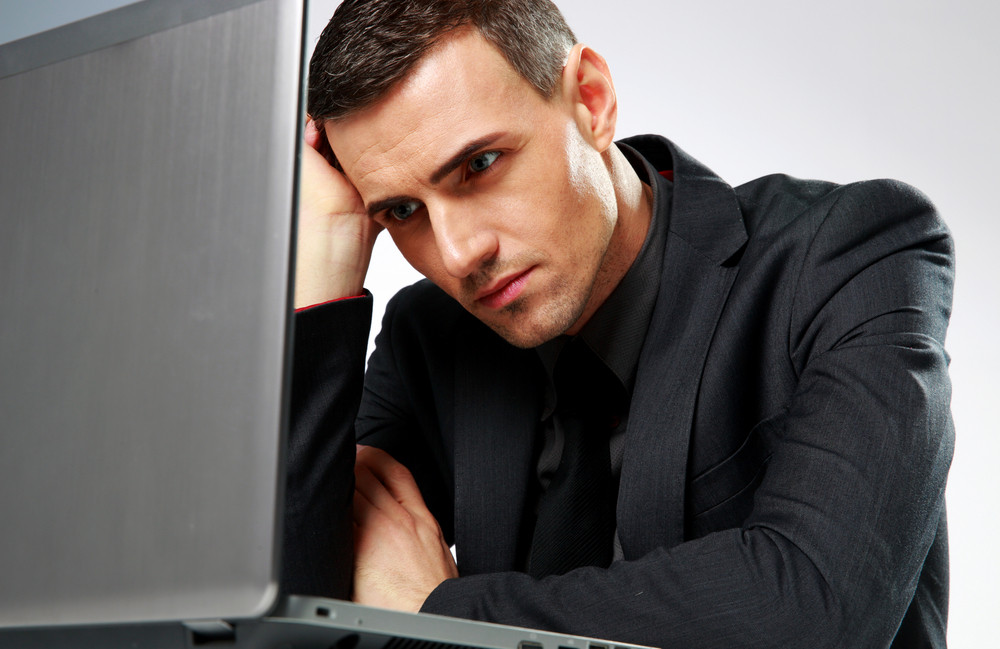 Thoughtful businessman sitting at the table with laptop on gray backgorund