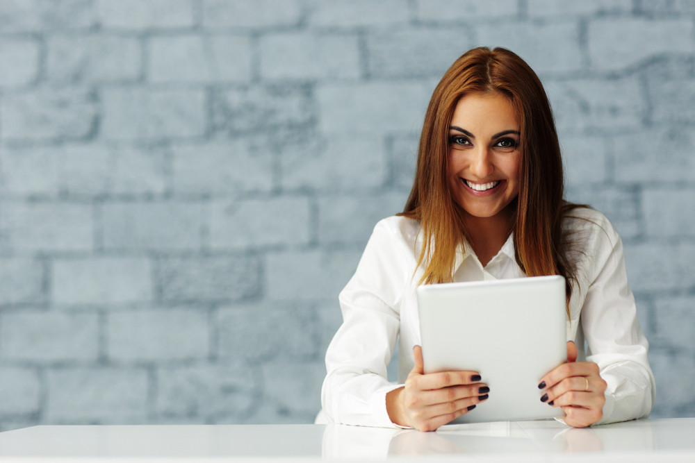 Laughing young businesswoman looking at camera
