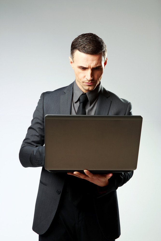 Confident businessman using laptop on gray background