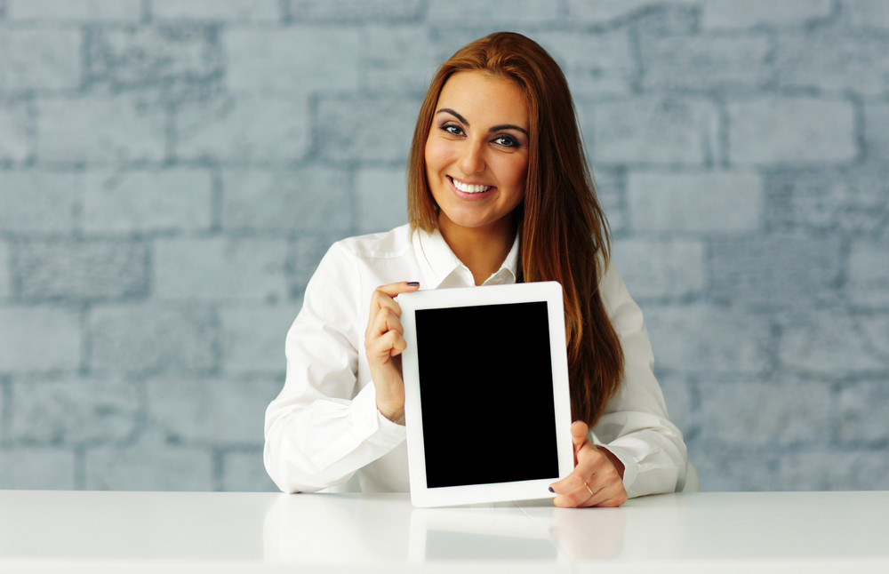 Young happy businesswoman showing tablet computer display