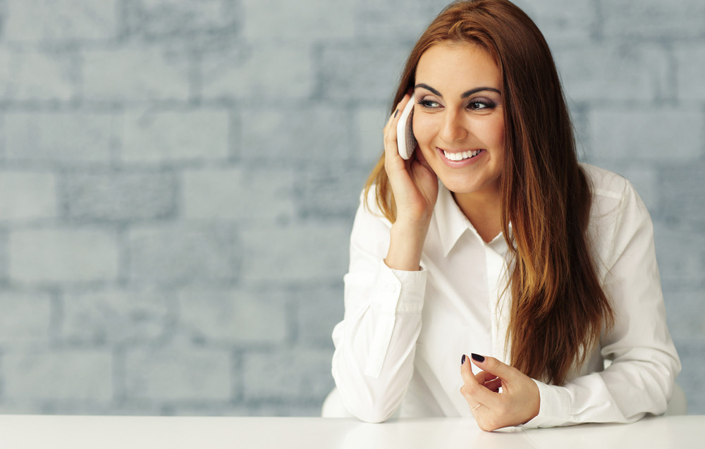 Happy businesswoman talking on phone and sitting at the table
