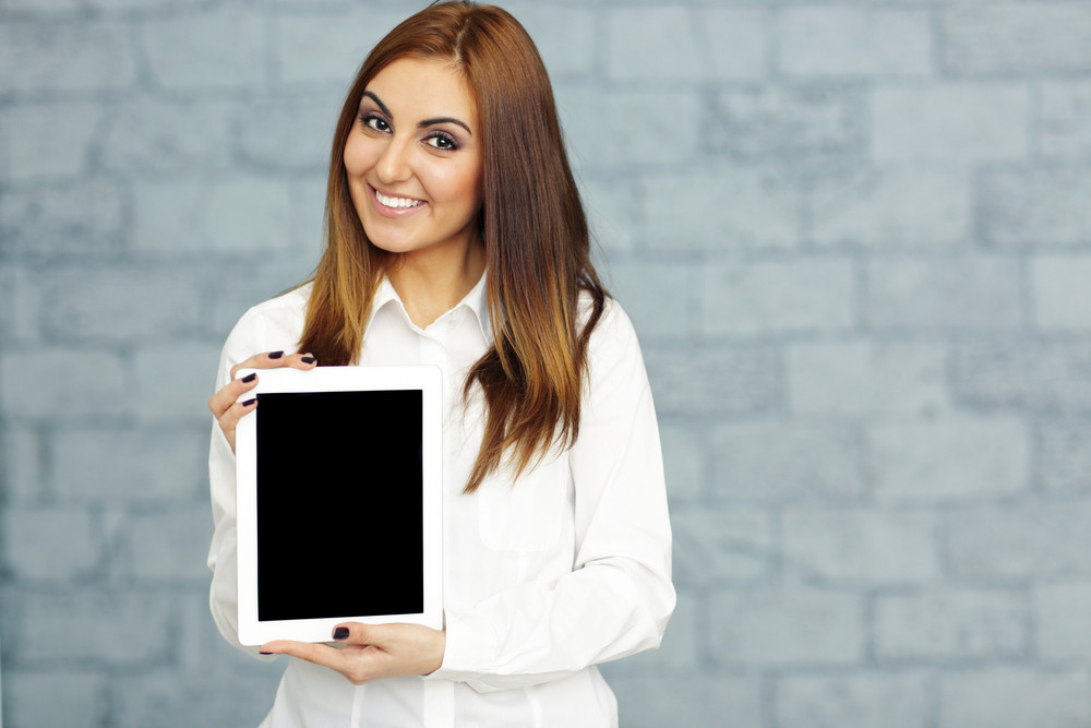 Happy confident businesswoman showing tablet computer display