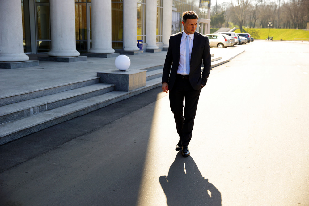 Confident businessman walking on the street
