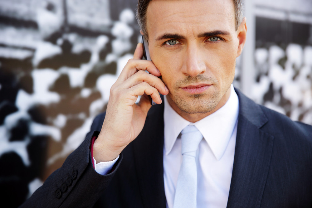 Confident businessman talking on the phone at office