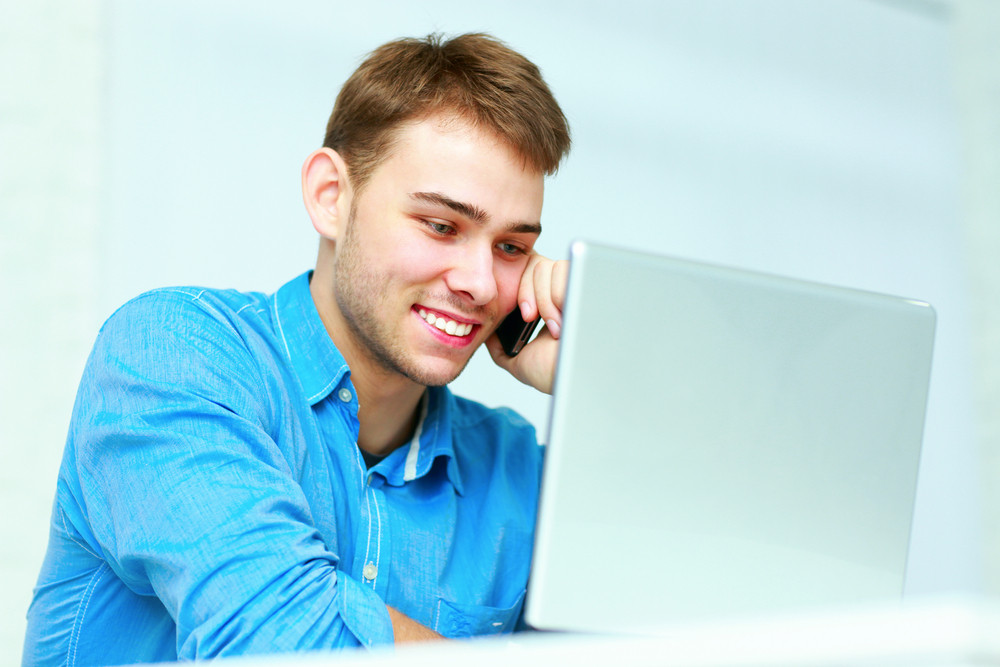 Young businessman sitting at the table with laptop and talking on the phone in office