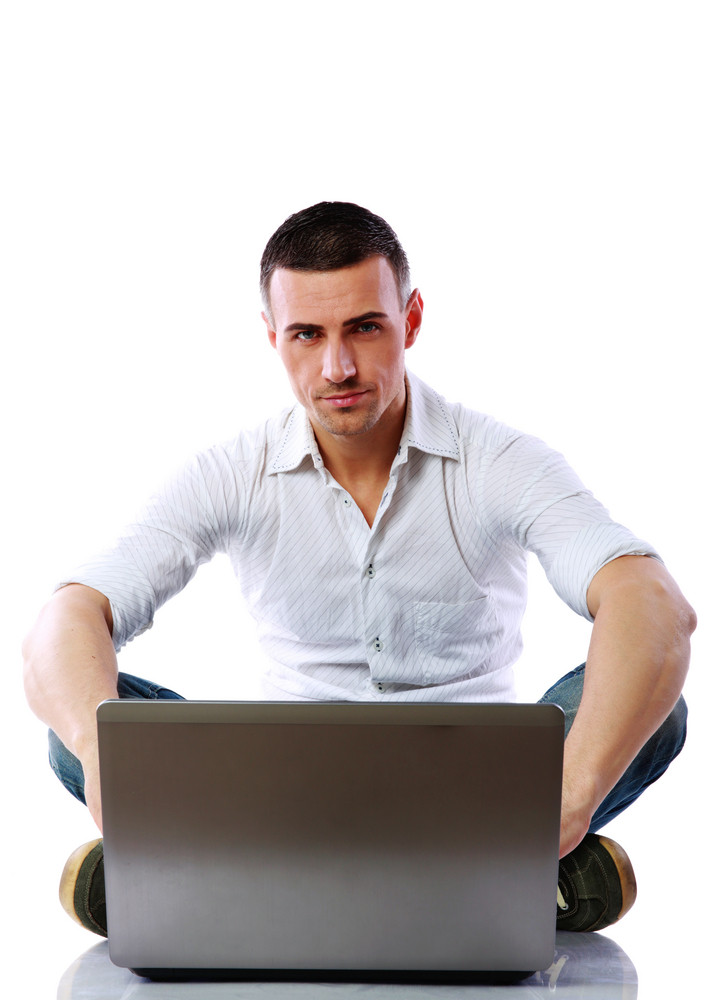 Confident man using laptop on the floor over white background